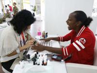 Robyn Gale, miembro de la selección de fútbol canadiense se prepara para una manicure en la Villa Olímpica.