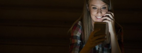 Gorgeous young woman standing with mobile phone at night street outdoors, female caucasian student reading text messages on her cell phone with reflected on her face screen light, blank screen phone