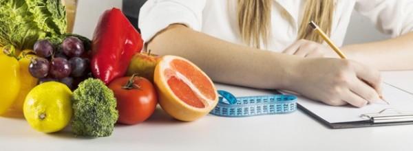 mano-dietista-que-escribe-tablero-comida-sana-escritorio_23-2147882179