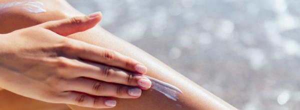 vista-primer-plano-mano-femenina-aplicar-protector-solar-su-pierna-cerca-mar_8353-6285