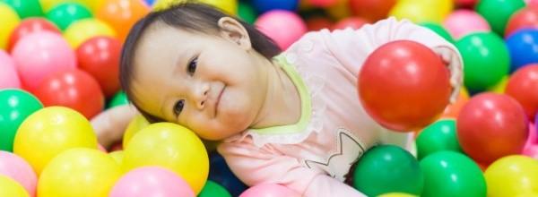 cara-emocional-bebe-sonriente-jugando-grupo-pelotas_34141-11